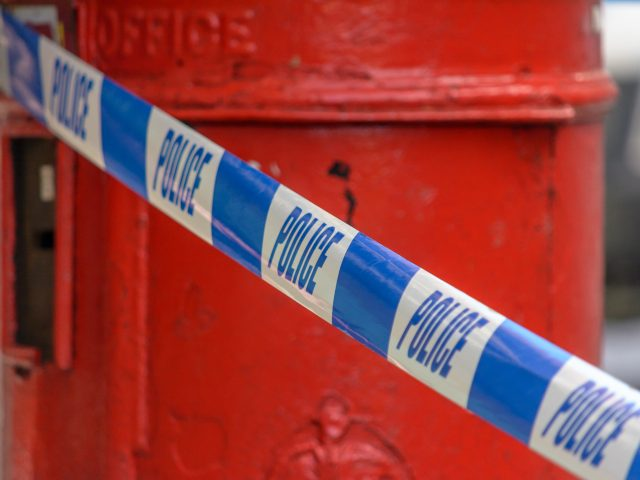 British Police Tape In Front Of Red Post Box, Shallow Depth of Field