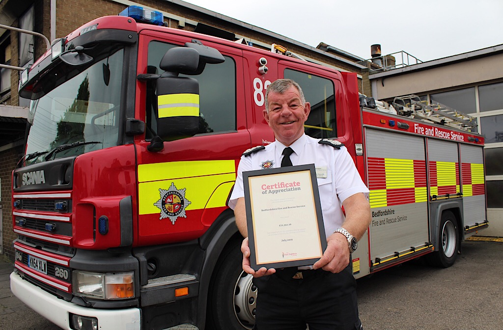 Chief Fire Officer Paul Fuller proudly holds the certificate