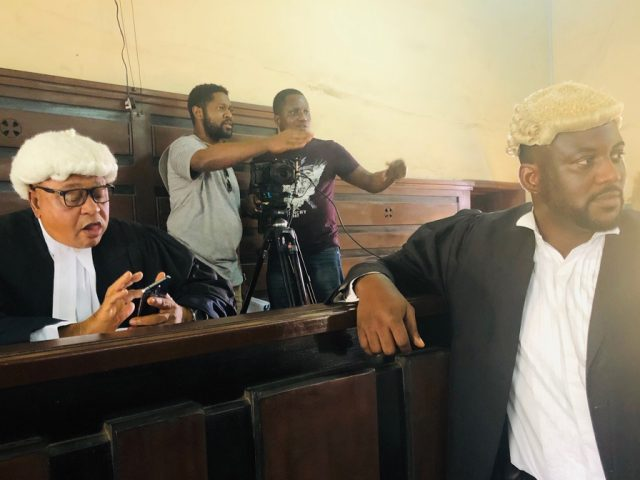 Matthew Jolaosho, in grey top, directing at a court room scene of Battle Within