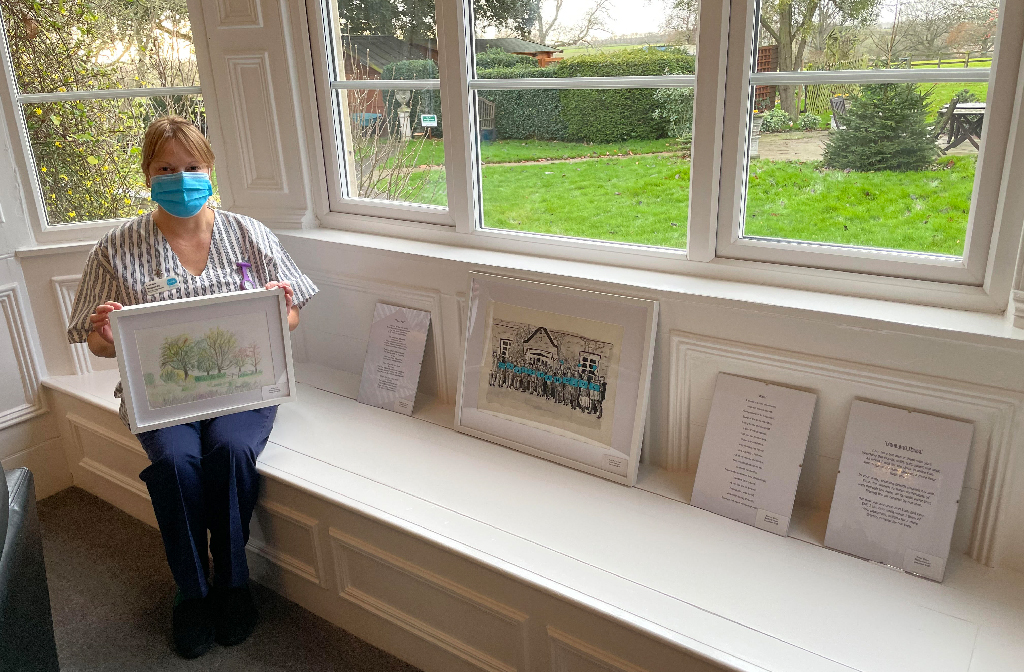 Sue Ryder St John's Hospice staff member, Lorraine Rosendale, admires the collection of thoughtful paintings and poems created by pupils from Bedford School